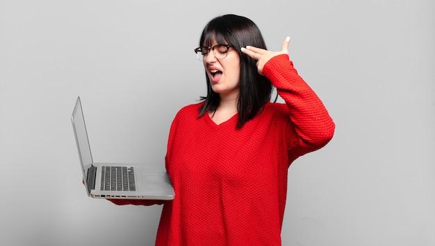 Plus size bella donna che sembra infelice e stressata, gesto di suicidio che fa segno di pistola con la mano, indicando la testa