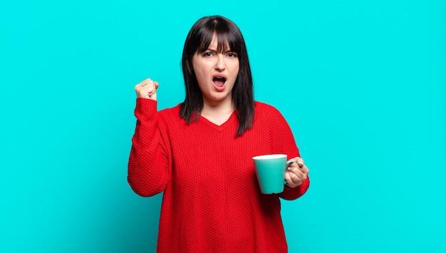 Plus size bella donna che grida in modo aggressivo con un'espressione arrabbiata o con i pugni chiusi celebrando il successo