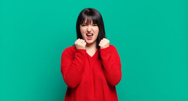 Plus size bella donna che grida in modo aggressivo con infastidito