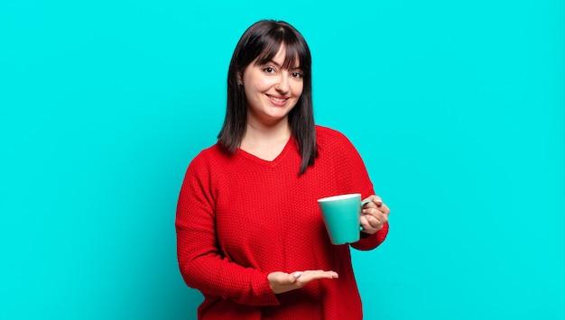 Plus size bella donna sorridente allegramente, sentendosi felice e mostrando un concetto nello spazio della copia con il palmo della mano