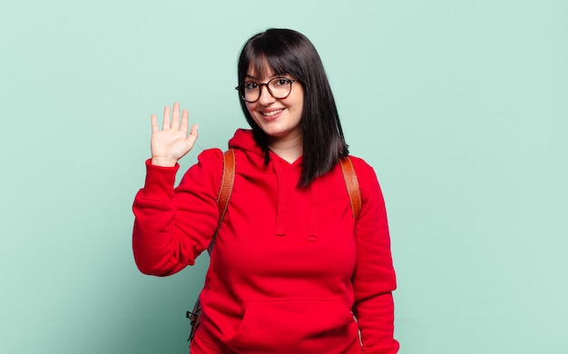 Taglie forti, bella donna che sorride allegramente e allegramente, agitando la mano, dandoti il benvenuto e salutandoti o salutandoti