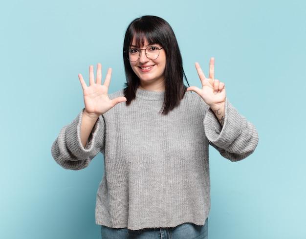 Plus size bella donna sorridente e dall'aspetto amichevole, mostrando il numero otto o ottavo con la mano in avanti, conto alla rovescia