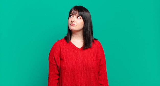 Plus size bella donna con un'espressione preoccupata, confusa, all'oscuro, alzando lo sguardo per copiare lo spazio, dubitando