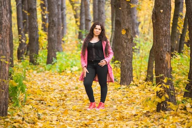 Taglie forti donna in pantaloni neri e giacca rosa in piedi nella foresta di autunno
