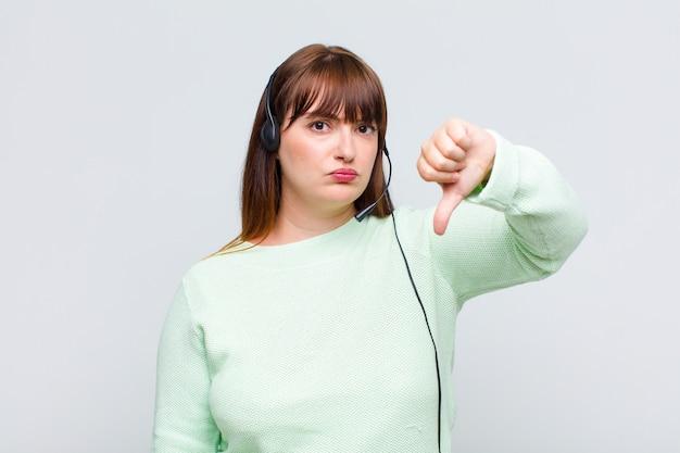 Donna taglie forti che si sente arrabbiata, arrabbiata, infastidita, delusa o scontenta, mostrando i pollici verso il basso con uno sguardo serio