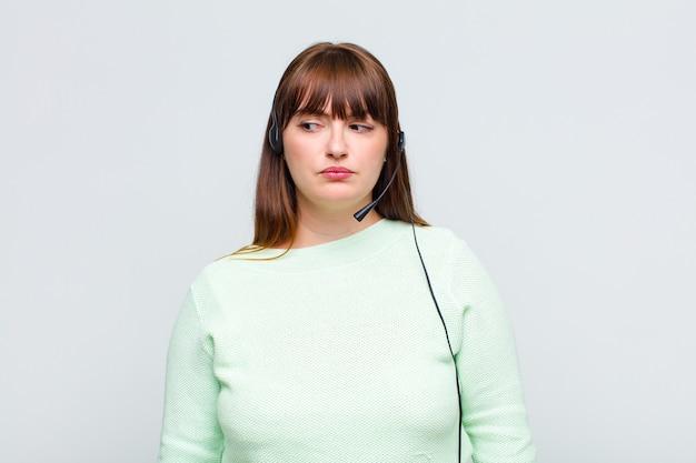 Donna di taglia forte che si sente triste, arrabbiata o arrabbiata e guarda di lato con un atteggiamento negativo, aggrottando la fronte in disaccordo