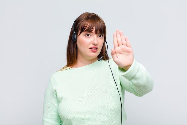 Plus size donna che sembra seria, severa, dispiaciuta e arrabbiata che mostra il palmo aperto che fa il gesto di arresto