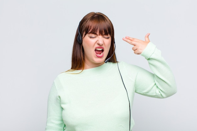 Plus size donna che sembra infelice e stressata, gesto di suicidio che fa segno di pistola con la mano, indicando la testa