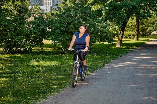 Plus size donna in sella alla bici nel parco