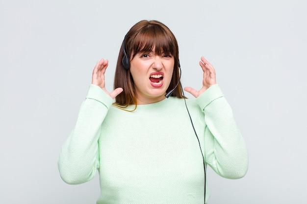 Plus size donna che urla con le mani in alto, sentendosi furiosa, frustrata, stressata e sconvolta