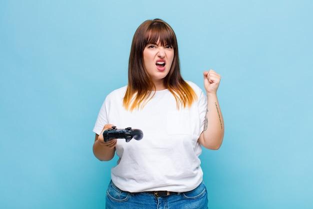 Plus size donna che urla in modo aggressivo con un'espressione arrabbiata o con i pugni chiusi per celebrare il successo