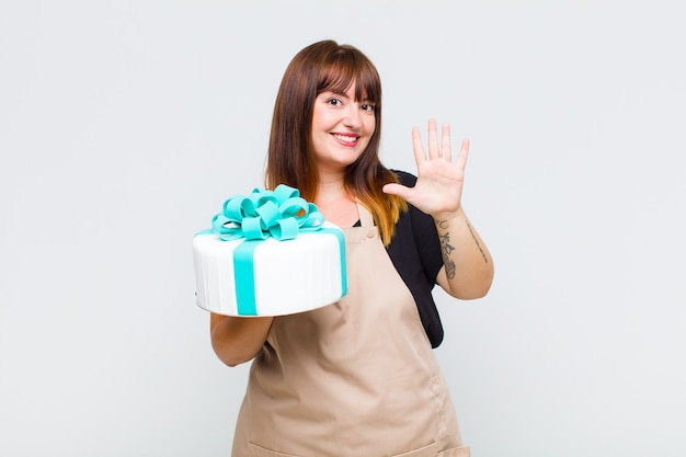 Plus size donna sorridente e dall'aspetto amichevole, mostrando il numero cinque o quinto con la mano in avanti, conto alla rovescia