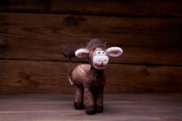 Giocattolo del toro della peluche su un fondo di legno. un peluche saluta lo spettatore. simbolo del nuovo anno 2021.