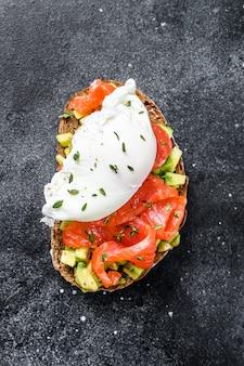 Uovo in camicia su pane tostato alla griglia con salmone affumicato e avocado