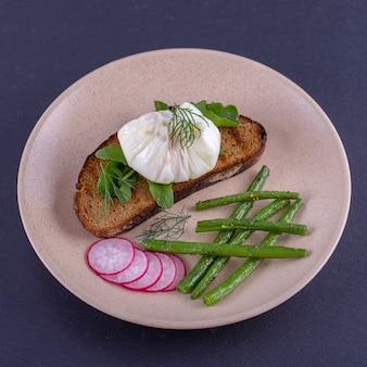 Uovo in camicia su un pezzo di pane con fagiolini fritti, ravanelli e rucola