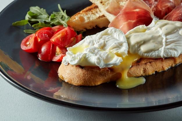 Uovo in camicia su un pezzo di pane con insalata, becon e pomodoro sul tavolo