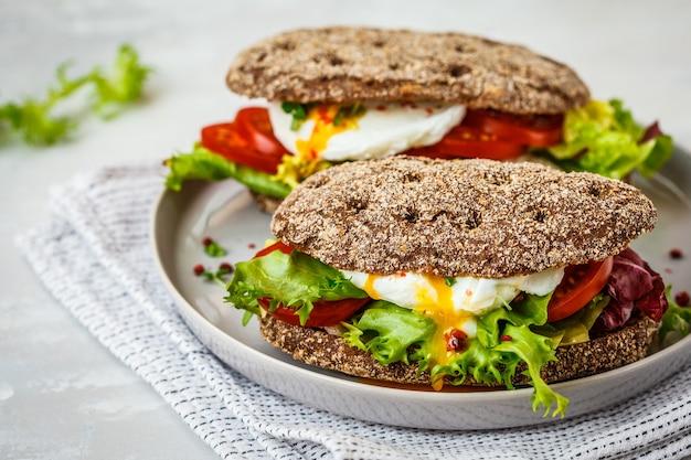 Panino con uovo in camicia con panino di segale e pomodoro su un piatto grigio.