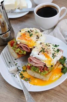 Uova in camicia con pomodori avocado fette di prosciutto su baguette per colazione