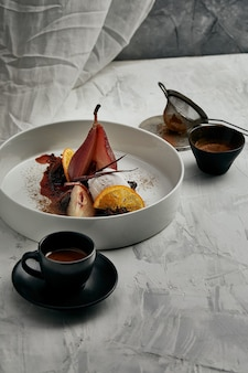 Pera affogata con gelato in salsa di vino rosso.