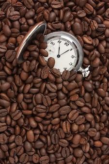 Orologio da tasca in un mucchio di chicchi di caffè