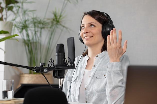 Creazione di contenuti audio podcast una bella donna europea podcaster o conduttrice radiofonica registra un podcast