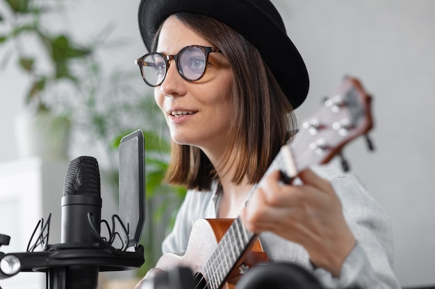 Podcast musica creazione di contenuti audio bella donna europea podcaster in un cappello con una chitarra o