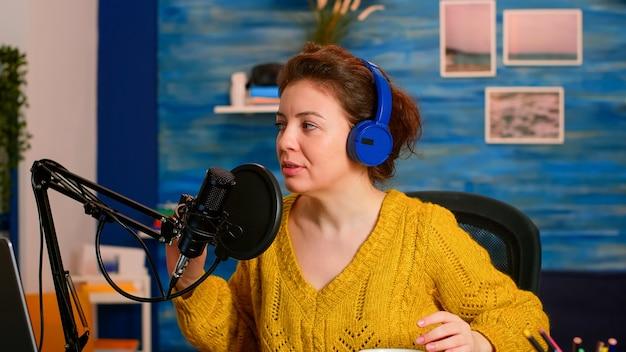 Podcaster che registra uno spettacolo online in studio utilizzando cuffie, microfono e laptop seduti nello studio podcast di casa