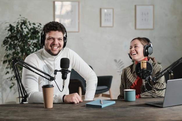 Podcaster che parla al microfono registrando podcast in studio con il suo collega