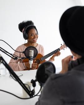 Podcaster donna afroamericana ed europea con cuffie e microfono