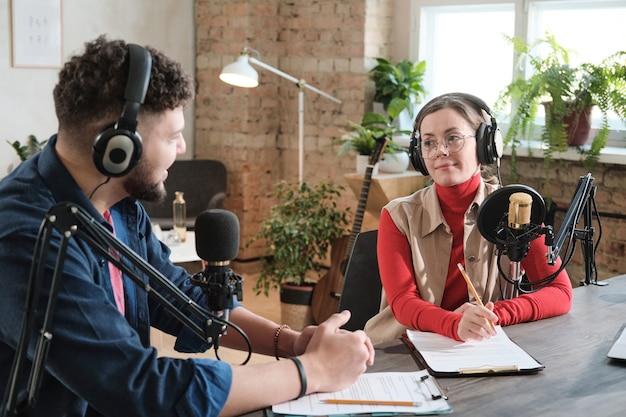 Podcaster che parlano ai microfoni registrando podcast in studio