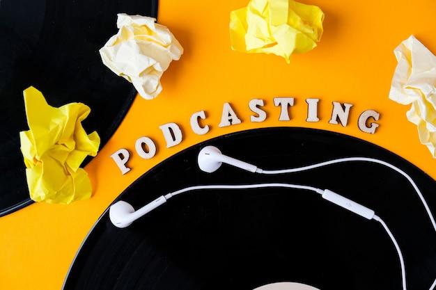 Podcasting lettering e album di dischi in vinile, cuffie carta stropicciata in stile minimalista su sfondo giallo. millenario. blogger, podcaster. stile retrò. audiolibri. nuovo episodio disponibile.