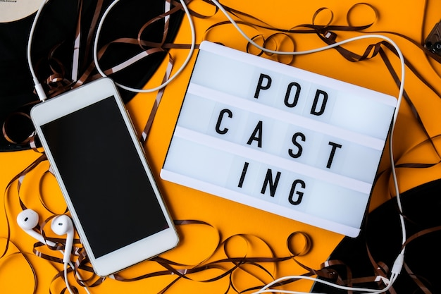 Podcasting lettering e dischi in vinile per audiocassette, cuffie per album e telefono cellulare. millenario. blogger, podcaster. stile retrò. audiolibri. nuovo episodio disponibile.