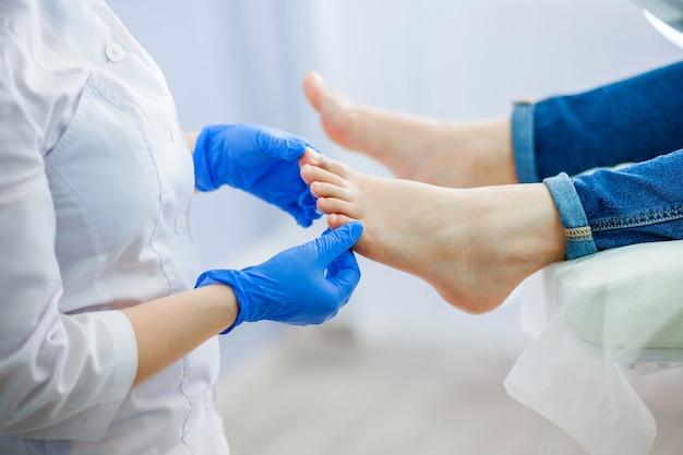 Il medico di podologia esamina il piede