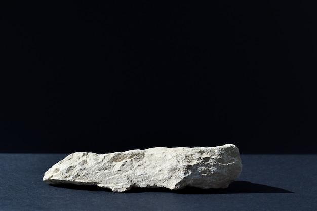 Il podio è uno sfondo nero con un palco, una vetrina in pietra e uno sfondo minimalista. presentazione dei cosmetici.