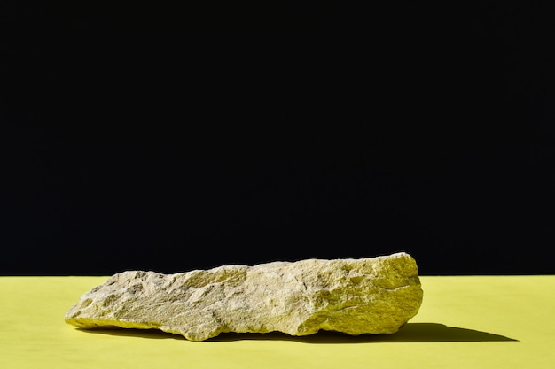 Il podio è uno sfondo nero e giallo con un palco, una vetrina in pietra e uno sfondo minimalista. presentazione dei cosmetici.
