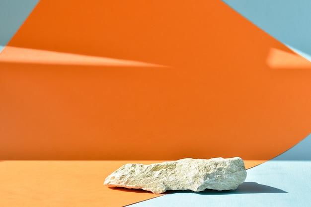 Il podio è uno sfondo arancio-blu con un palco, una vetrina in pietra e uno sfondo minimalista. presentazione dei cosmetici.