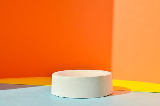 Il podio è uno sfondo giallo-arancio con una figura geometrica in cemento. una scena con una vetrina in cemento. sfondo minimalista. presentazione dei cosmetici.