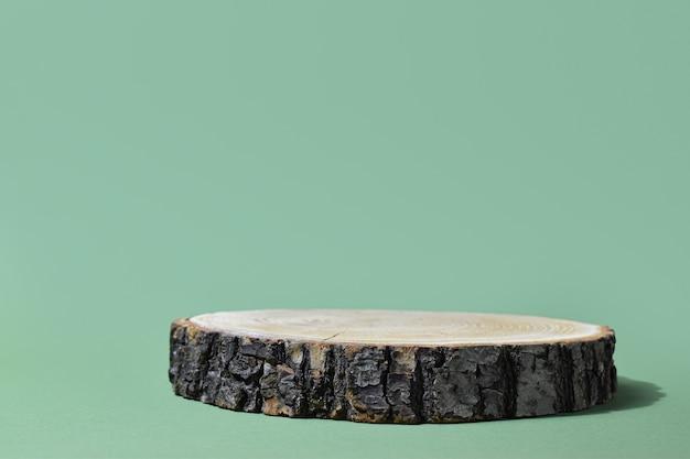 Podio per la presentazione del prodotto. una scena minimalista di un albero abbattuto si trova su uno sfondo verde.