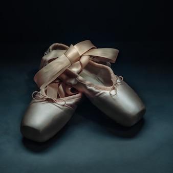 Scarpe da danza classica scarpe da ballo con un arco di nastri splendidamente piegati su uno sfondo scuro.