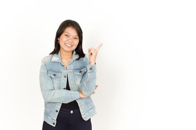Indicando da parte della bella donna asiatica che indossa giacca di jeans e camicia nera isolata su white