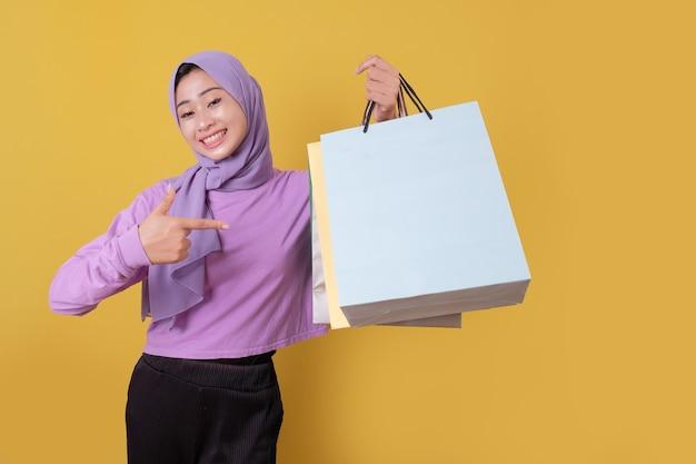 Indicare di bella donna asiatica che mostra le borse della spesa, indossando la maglietta viola