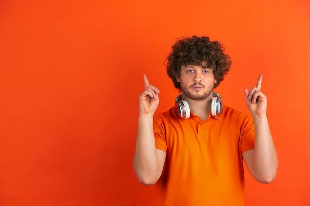 Indicare, scegliere. ritratto monocromatico del giovane caucasico sullo studio arancione.