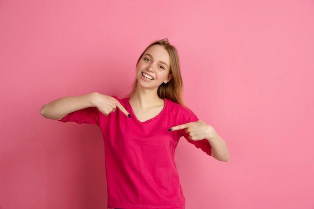 Indicando se stessa. ritratto della giovane donna caucasica in studio rosa