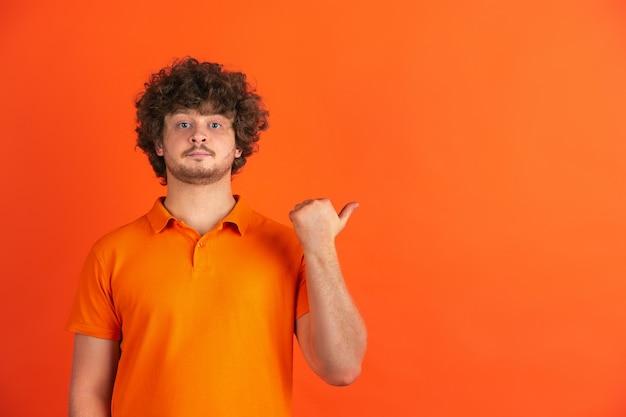 Indicando di lato. ritratto monocromatico del giovane caucasico sullo studio arancione.
