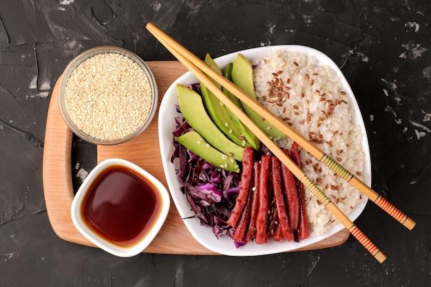 Poke ciotola cibo hawaiano. un piatto di riso, salmone, avocado, cavolo e formaggio. vicino a skunk e salsa di soia su sfondo nero. vista dall'alto