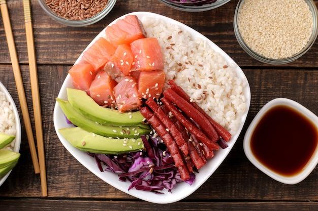 Poke ciotola cibo hawaiano. un piatto di riso, salmone, avocado, cavolo cappuccio e formaggio, accanto a sesamo e salsa di soia. su un tavolo di legno marrone. vista dall'alto