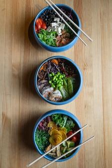 La poke bowl è l'ultima tendenza nel settore alimentare, una ciotola con verdure e salmone su fondo in legno