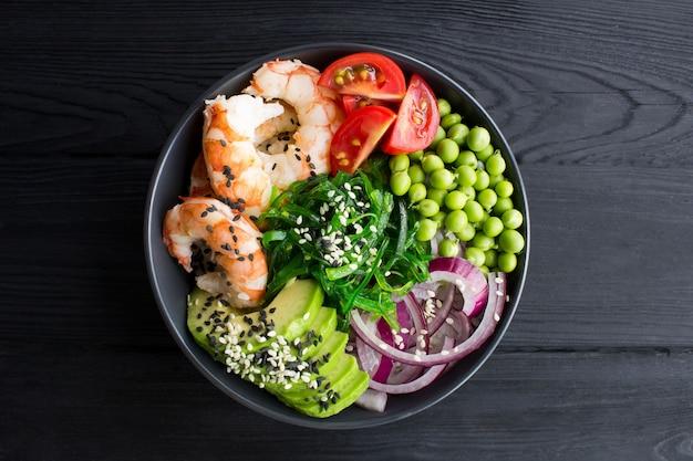 Colpisci la ciotola con gamberi rossi e verdure nella ciotola scura