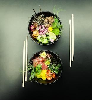 Insalate di poke con tonno e manzo in ciotole sul tavolo due ciotole di insalata di poke con le bacchette su un gr...