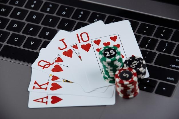 Carte da poker e pile di fiches da poker su un computer portatile. casinò e poker online concept.
